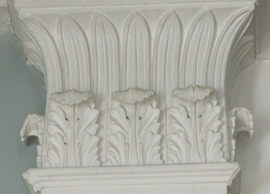 Ornamentation in the double parlors includes carved pilasters with Corinthian capitals and double anthemia.
